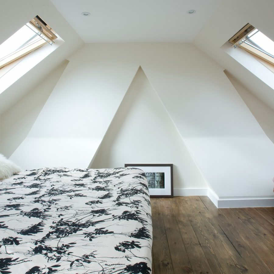 From the inside of a London loft conversion, we see 2 windows, white walls, and a white ceiling.